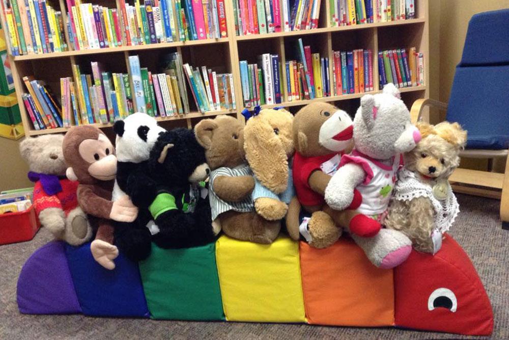 À l'intérieur de la bibliothèque Champlain, une collection d'animaux en peluche assis ensemble comme s'ils montaient dans un train sur des coussins de couleur arc-en-ciel