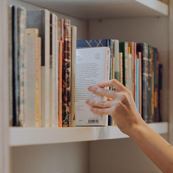 Photo of a hand touching books on a bookshelf 2