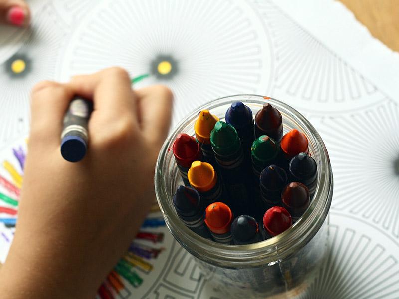 une photo d'un enfant tenant un crayon et dessinant une image